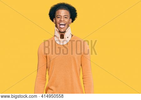 African american man with afro hair wearing cervical neck collar sticking tongue out happy with funny expression. emotion concept.