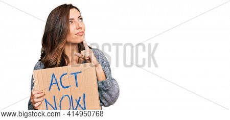 Young brunette woman holding act now banner serious face thinking about question with hand on chin, thoughtful about confusing idea