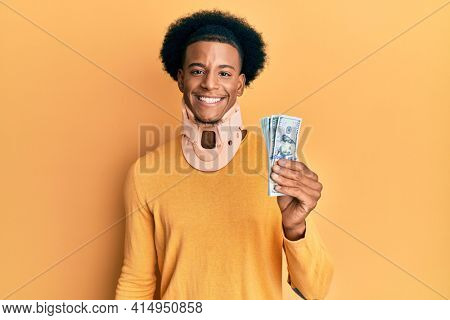 African american man with afro hair wearing cervical neck collar and holding money from insurance looking positive and happy standing and smiling with a confident smile showing teeth