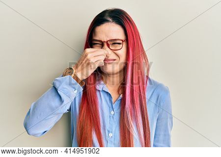 Young caucasian woman wearing casual clothes and glasses smelling something stinky and disgusting, intolerable smell, holding breath with fingers on nose. bad smell