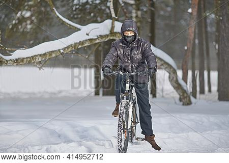 Active Winter Recreation. A Teenager In A Buff And Black Clothes Rides A Bike In Winter