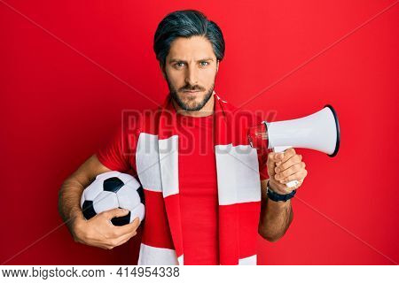 Young hispanic man football hooligan holding ball using megaphone skeptic and nervous, frowning upset because of problem. negative person.