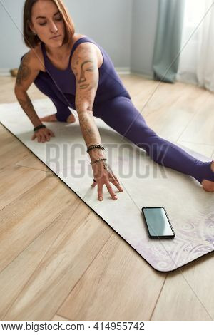 Young Girl Exercising At Home Next To The Phone. Brunette Trainer Conducting Online Workout At Home