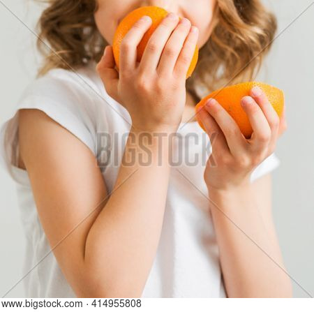 A Little Girl In A White T-shirt Holds Two Orange Slices In Her Hands And Sniffs Them. Vertical Phot