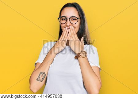 Young hispanic woman wearing casual white t shirt laughing and embarrassed giggle covering mouth with hands, gossip and scandal concept