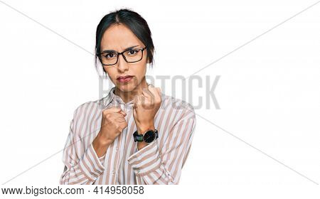 Young hispanic girl wearing casual clothes and glasses ready to fight with fist defense gesture, angry and upset face, afraid of problem