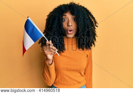 African american woman with afro hair holding france flag scared and amazed with open mouth for surprise, disbelief face