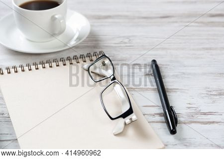Top View Office Desk With White Cup Of Coffee. Flat Lay Vintage Wooden Table With Spiral Notebook, G