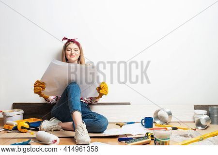 Happy Girl Sitting On Floor With Paper Blueprint. Home Remodeling After Moving. Construction Tools A