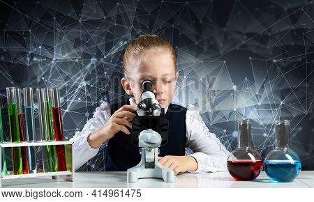 Little Girl Scientist Looking Through Microscope In Classroom At Chemistry Lesson. School Chemical L