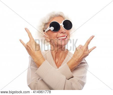 Lifestyle, emotion and old people concept: Senior woman wearing big sunglasses doing funky action isolated on white background