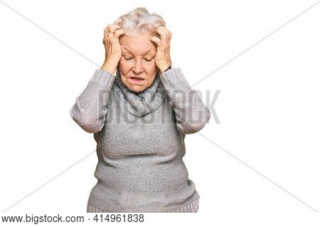 Senior grey-haired woman wearing casual winter sweater suffering from headache desperate and stressed because pain and migraine. hands on head.