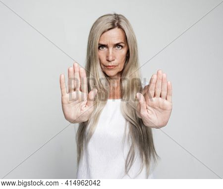 Senior grey-haired woman doing stop sign with serious and confident expression over grey background