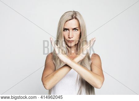 Elderly woman with long gray hair wearing casual style rejection expression crossing arms doing negative sign, angry face over grey background.