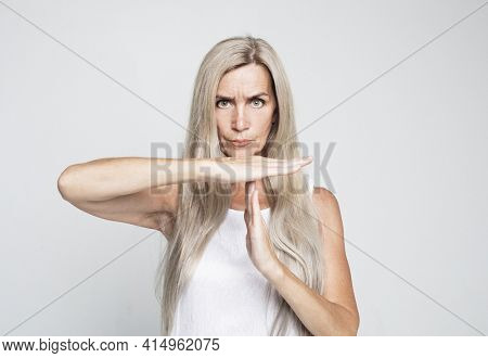Gesture, prohibition and old people concept: Senior woman with long grey hair making time out sign over grey background