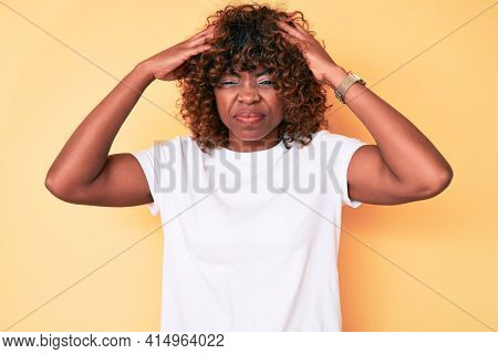 Young african american woman wearing casual white t shirt with hand on head, headache because stress. suffering migraine.