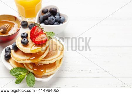 Healthy breakfast with pancakes and orange juice. Homemade american pancakes with berries and honey. With copy space