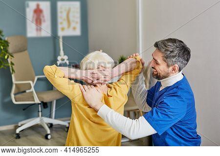 Back Treatment And Scoliosis Correction To Elderly. Positive Orthopedist Doing Treatment Senior Woma