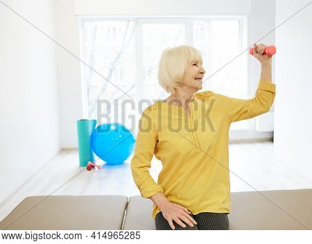 Senior Patient While Exercise Treatment Using Dumbbells For Strengthening Arm Muscles . Rehab At A M