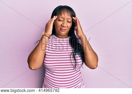 Middle age african american woman wearing casual clothes with hand on head, headache because stress. suffering migraine.