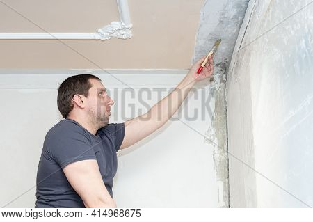 The Process Of Priming Concrete Close-up. The Worker Primes The Wall And Ceiling With A Brush.
