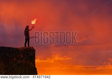 Concept Of Confidence - Man On A Cliff With A Torch And Sword, Orange Sky Background
