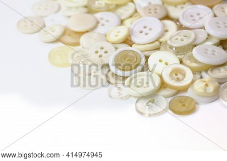 White And Beige Buttons On A White Background. Old Vintage Buttons Close Up. Copy Space. Side View.