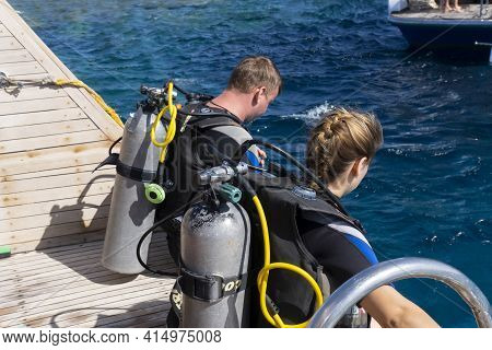 Two Divers, Man And Woman, In Swimming Diving Suits Sit At Boat Before Jumping At Blue Water And Pre