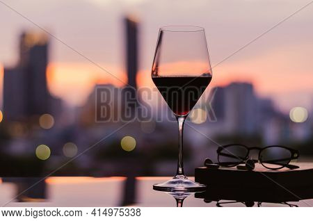 A Glass Of Red Wine With Spectacles And Ear Pod On Book Put On Table With City Background. Stay Home