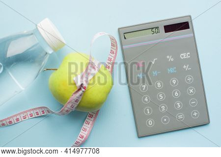 Calculator, Bottle Of Water, Apple With Measuring Tape On Blue Background. Weight Loss, Counting Cal