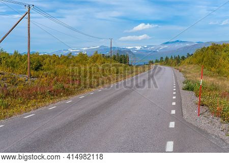 Road With Power Line Next To It In Remote Wilderness Of Swedish Lapland. Sunny Day Of Arctic Autumn.
