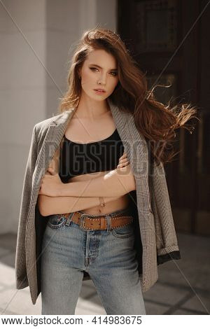 Fashion Outdoor Shoot Of A Beautiful Model Girl In Trendy Jacket And Jeans