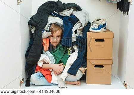 Kid Hiding Among Messy Clothes Inside Closet. Organization And Storage Of Clothes At Home. Mess In T
