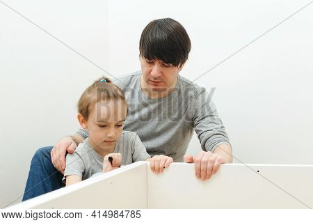Dad And Little Son Assembling Furniture At Home. Furniture Assembly Yourself. Father Helps His Son T