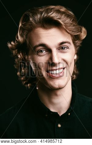 Portrait of a handsome young man with wavy blond hair smiling looking at camera. Black background with copy space. Men's beauty.
