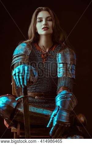 A beautiful noble warrior woman in chainmail and plate armor sits holding her sword. Medieval knight.