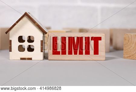 Limit. Text In Black Letters On Wood Blocks. Near The House Figurine. Be Ready To Buy A House