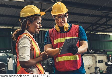 Two Skillful Factory Engineer Or Worker Discussing Project On Tablet Computer . Industrial People An