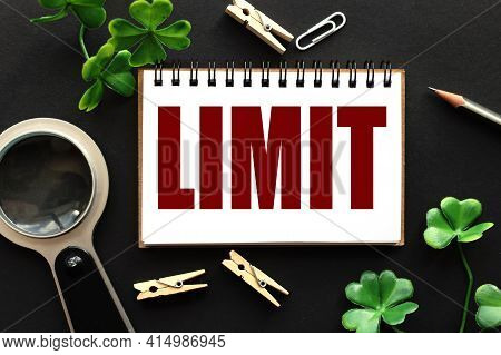 Limit.text On White Paper On Black Background. Plants. Magnifier