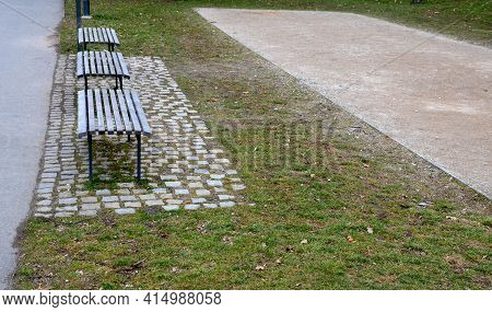 Walking Path Through The Park Where There Is Also A Bowling Court Made Of A Beige Sandy Surface In T