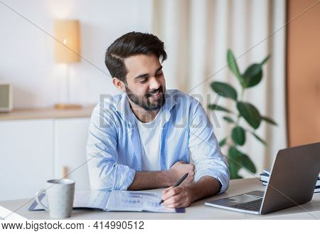 Successful Eastern Entrepreneur Working With Documents And Laptop At Home Office