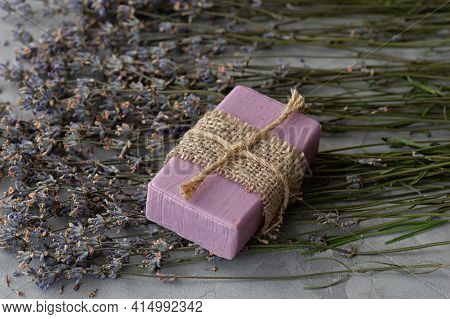Handmade Soap With Natural Ingredients And Dry Lavender Flowers On A Gray Concrete Background. Close