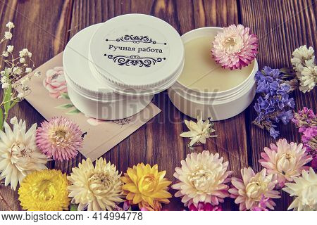 Handmade Cream On A Dark Wooden Surface Surrounded By Bright Dried Flowers. Healthy Lifestyle, Natur
