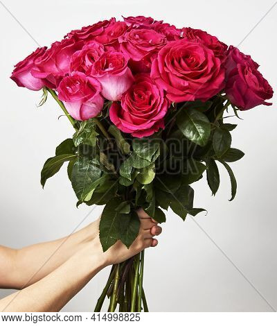 Hand Holding A Bouquet Of Pink Roses On White Background