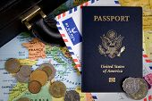 USA passport foreign coins and briefcase sit on a world map for an international business travel concept. poster