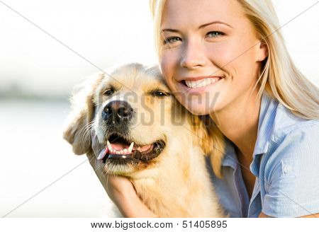 Close up of blond woman embracing golden retriever poster
