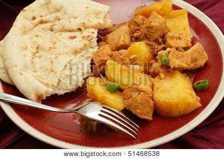 Goan chicken and potato vindaloo curry, cooked in a vinegar and spice sauce and served with a slice of flat bread
