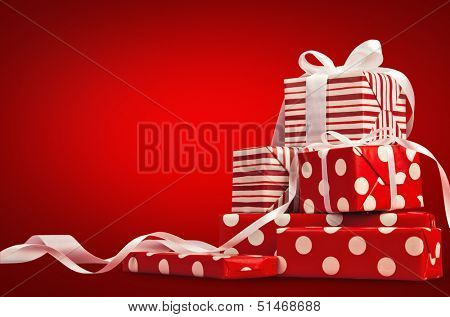 Christmas gifts with ribbon on a red background