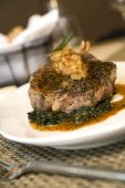 Braised leg of lamb served on bed of chopped spinach and au jus. poster