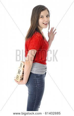 A happy young teen waving good-bye as she holds alphabet blocks showing the letters